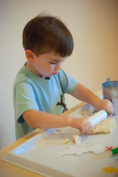 L rolling out his play dough