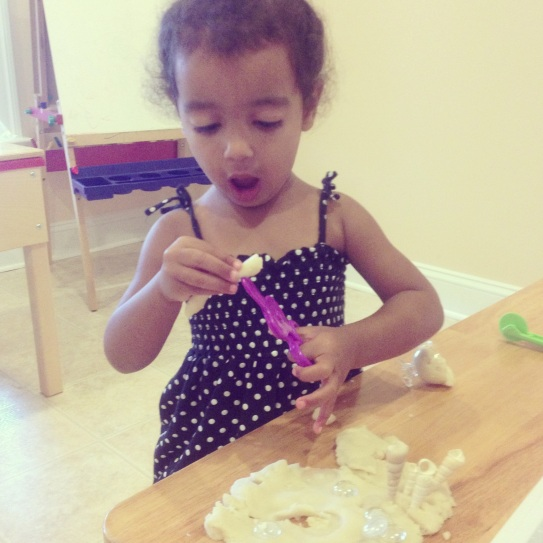 M practicing her cutting skills with play dough