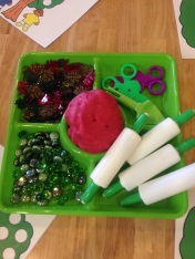 play dough tray filled with gems, leaves, and rolling pins for exploration