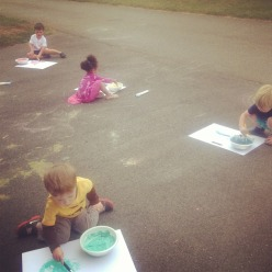 Lots of little children busy painting outside.