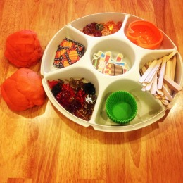 Pumpkin pie play dough tray. Play dough is offered with lots of objects to facilitate play.