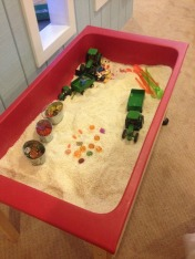 Pumpkin Patch sensory bin, filled with rice, pumpkin gems, tractors and little people for imaginative sensory play.