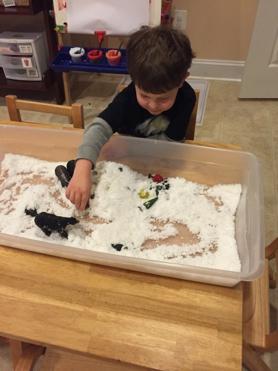 """sensory tray with pretend snow and characters from """"The Mitten"""""""